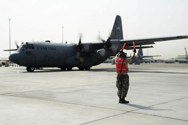 Senior Airman Steven Engels, 379th Expeditionary Aircraft Maintenance Squadron crew chief, marshals a C-130 Hercules on the flight line June 28, 2016, at Al Udeid Air Base, Qatar. (U.S. Air Force photo/Senior Airman Janelle Patiño)