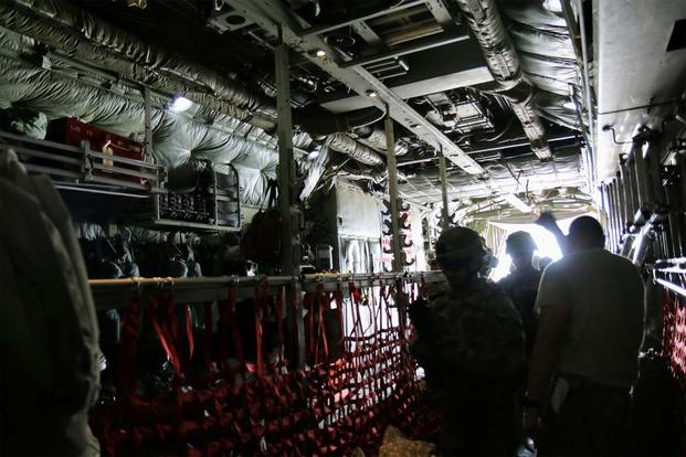 A Variety of U.S. and coalition military personnel board a C-130 for transport. (Photo: Oriana Pawlyk/Military.com)