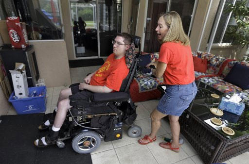 Chris Ott, right, helps her son, former Marine John Thomas Doody. J.T., who was shot while serving in Fallujah, Iraq.,
