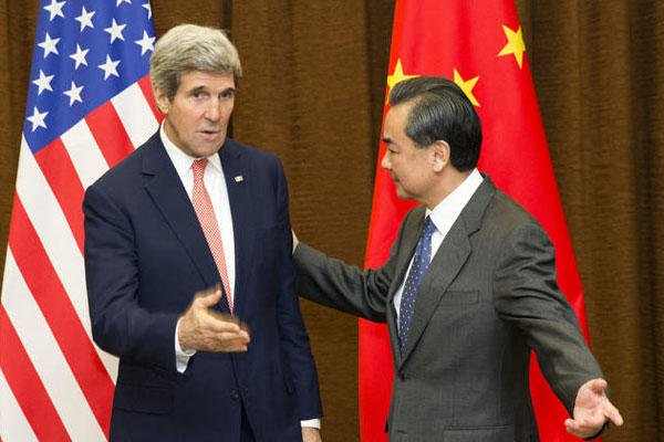 U.S. Secretary of State John Kerry, left, is greeted by Chinese Foreign Minister Wang Yi at the Ministry of Foreign Affairs in Beijing, China Friday, Feb. 14, 2014.