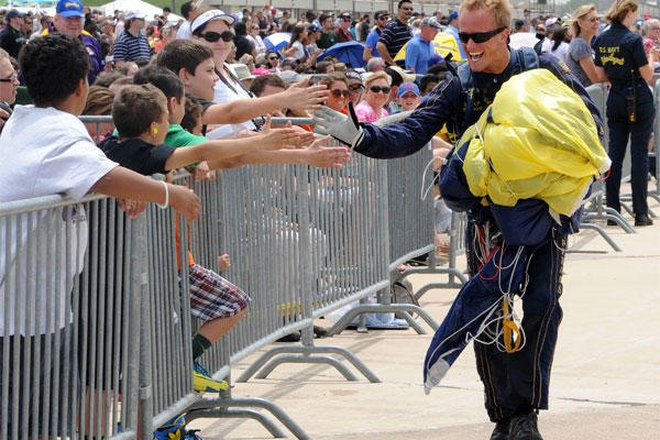 Special Warfare Operator 2nd Class T.J. Amdahl, a member of the Navy Parachute Team, the Leap Frogs, is greeted by the crowd following a demonstration jump at the Air Power Expo air show at Naval Air Station Fort Worth.