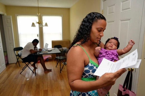 In this June 18, 2014 photo, Army Sgt. LaQuisha Gallmon, right, reads a letter from the Veterans Affairs Depart, as she holds her 2-month-old Abbagayle in Greenville, S.C. (Richard Shiro/AP)