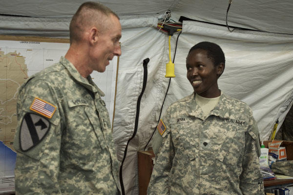 Army Maj. Gen. Gary Volesky recognizes Army Spc. Rysper Sirma for her exemplary performance while supporting Operation United Assistance at the Barclay Training Center, Monrovia, Liberia, Dec. 26, 2014. (U.S. Army photo by Staff Sgt. V. Michelle Woods)