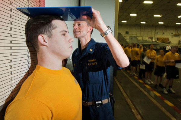 Command Fitness Leader Lt. Bradley Lester measures a Sailor's height while conducting the body composition assessment. (U.S. Navy photo by Mass Communication Specialist 2nd Class James R. Evans)