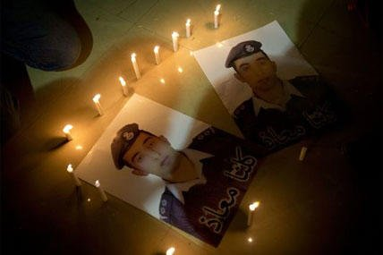 Members of Al-Kaseasbeh, the tribe of Jordanian pilot, Lt. Muath al-Kaseasbeh, who is held by the Islamic State group militants, light candles by posters with his picture. (AP Photo/Nasser Nasser)
