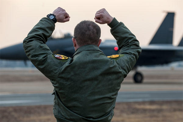 "Maj. Dean Laansma gives the 80th Fighter Squadron ""Crush 'em"" gesture to an F-15K Slam Eagle as it taxis during exercise Buddy Wing 15-2 Feb. 5, 2015, at Daegu Air Base, South Korea. (U.S. Air Force photo/Senior Airman Katrina Heikkinen)"