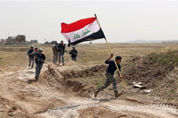 A member of the Iraqi security forces plants the national flag on March 30, 2015, as the forces surround Tikrit, Iraq, during clashes to regain the city from Islamic State militants. (AP Photo/Khalid Mohammed)