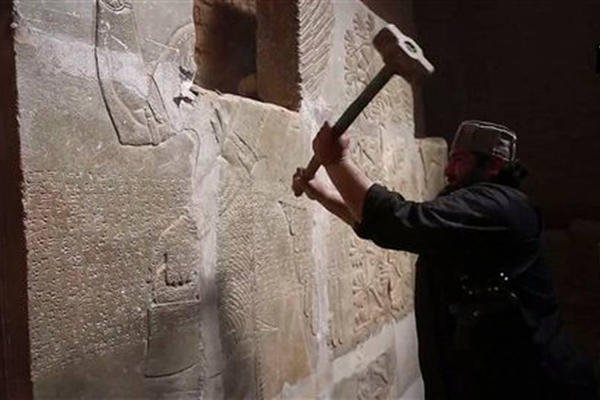 This image made from video posted online by a group affiliated with the Islamic State group on April 11, 2015, purports to show a militant taking a sledgehammer to an Assyrian relief at the site of the ancient city of Nimrud. Image via AP.