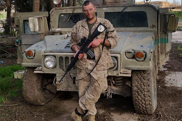 In this Feb. 26, 2015 photo, Jamie Lane, 29, an American veteran, poses for a picture in front of an Iraqi Army Humvee captured and later abandoned by Islamic State militants in Tel Hamis, Syria. (Courtesy Jamie Lane via AP)