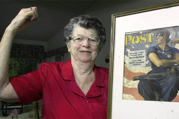 "In this May 22, 2002 file photo, Mary Doyle Keefe poses at her home in Nashua, N.H., with the May 29, 1943, cover of the Saturday Evening Post for which she had modeled as ""Rosie the Riveter"" in a Norman Rockwell painting. (AP Photo/Jim Cole)"