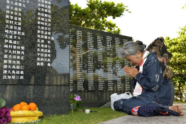 An elderly woman prays in front of the Cornerstone of Peace, monument walls on which the names of all those who lost their lives, at Peace Memorial Park in Itoman on Okinawa islands, June 23, 2015. (Hiroko Harima/Kyodo News via AP)