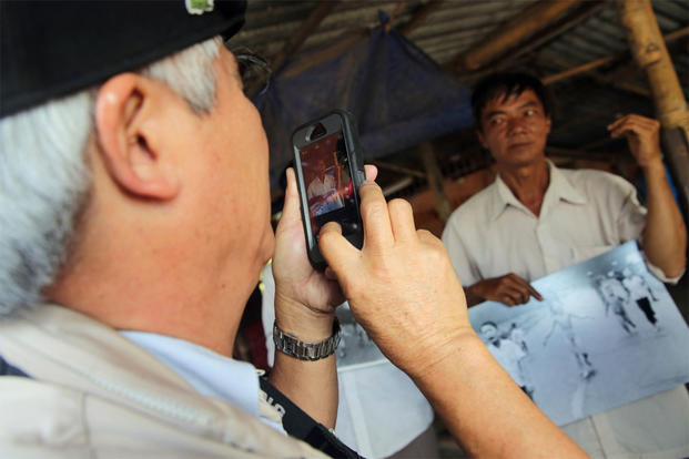 Pulitzer winning photographer Nick Ut uses a smartphone to take a photo of Ho Van Bon holding the iconic 'Napalm girl' image Ut captured 43 years ago on Monday, June 8, 2015 in Trang Bang, Vietnam. (AP Photo/Na Son Nguyen)