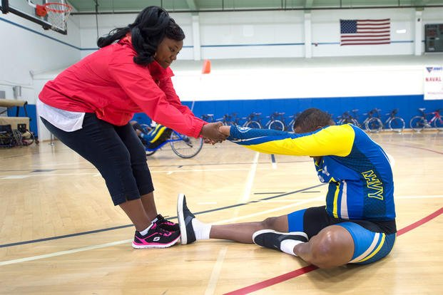 Ida Malone helps her husband, Navy Chief Petty Officer Averill Malone, stretch before cycling during the Navy's training camp for the 2015 DoD Warrior Games at Ventura County Naval Station Port Hueneme, June 3, 2015. DoD photo by EJ Hersom