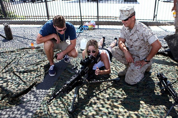 Lance Cpl. Matthew Ritter, a heavy equipment operator with Bulk Fuel Company, 7th Engineer Support Battalion, shows a couple a weapons system during San Diego Fleet Week 2015 at Naval Base Coronado, Calif. (U.S. Marine Corps/Sgt. Laura Gauna)