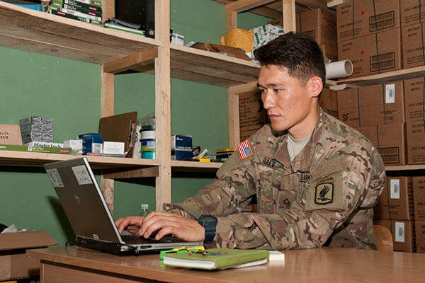 U.S. Army Pfc. Aidarbek Raev updates unit supply inventory records in Panevezys, Lithuania. Raev is Dog Company's supply specialist and performs the duties of a soldier three tiers above his current rank. (U.S. Army/Sgt. Jarred Woods)