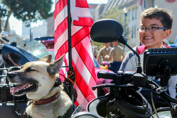 A young boy sits on a motorcycle with a dog while waiting for the Italian heritage parade to start on Oct. 11., as part of San Francisco Fleet Week 2015. Photo By: Cpl. Joshua Murray