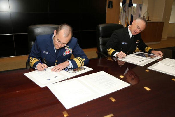 Coast Guard Vice Adm. Charles Michel, deputy commandant for operations, and NOAA Vice Adm. Michael Devany, deputy under secretary for operations, sign the Fleet Plan Agreement letter of promulgation Oct. 8, 2014. (Photo provided to Coast Guard by NOAA)