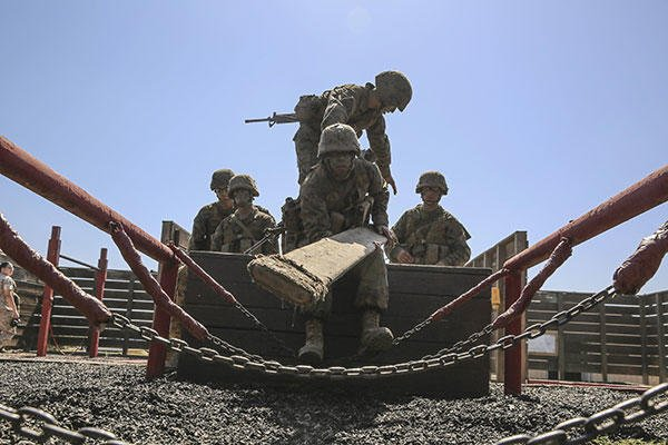 Marine Corps Pfc. Mason A. Davis lays a board across a chain bridge during the 12 Stalls event at Edson Range, Marine Corps Base Camp Pendleton, Calif., Sept. 23, 2015. (U.S. Marine Corps/Cpl. Jericho Crutcher)