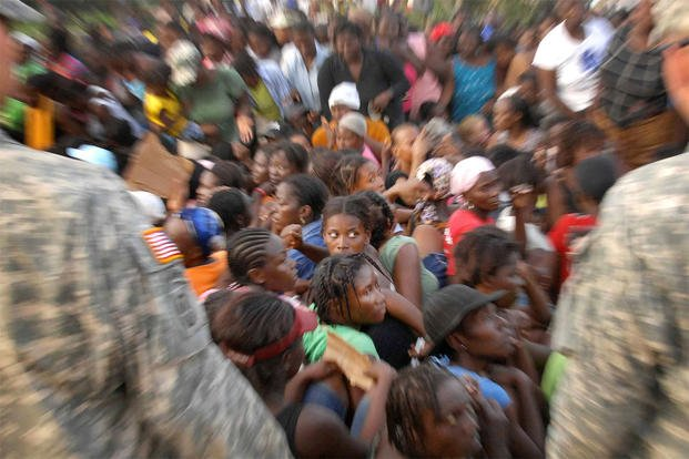 A crowd of women sit after a call for order during the distribution of humanitarian aid in Port-au-Prince, Haiti, Jan. 19, 2010. (DoD photo by Fred W. Baker III)
