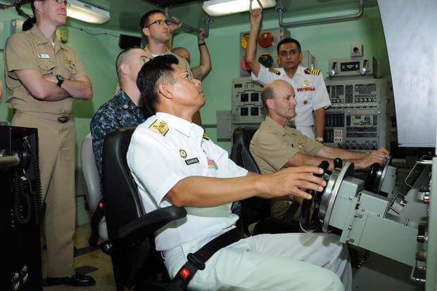 Rear Adm. Abdul Rahman, commander, Royal Malaysian Navy Submarine Force, center, and Rear Adm. William Merz, commander, Submarine Group Seven, operate a submarine dive simulator, Dec 1. (Photo: Mass Communication Specialist 2nd Class Zac Shea)