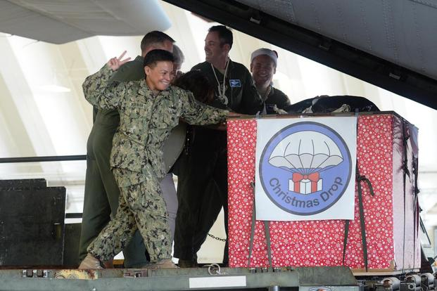 Rear Adm. Babette Bolivar counts down before pushing a crate containing donated goods into a C-130 Hercules during the Christmas Drop Push Ceremony Dec. 8, 2015, at Andersen Air Force Base, Guam. (Photo: Staff Sgt. Benjamin Gonsier)