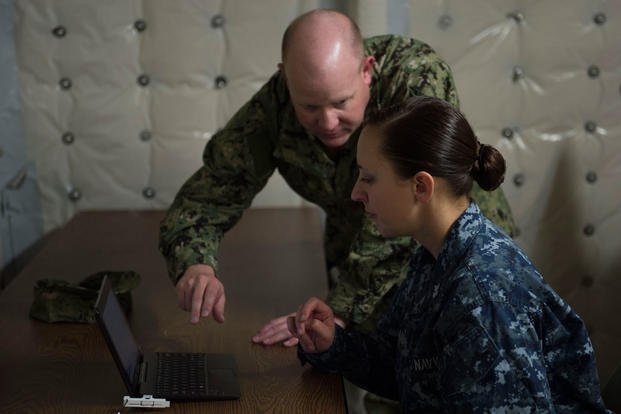 Lt. Cmdr. Jason Smith aids Hospital Corpsman 1st Class Vanessa Poland, assigned to USNS Spearhead, in completing forms prior to deployment. (Photo: Mass Communication Specialist 3rd Class Amy M. Ressler)