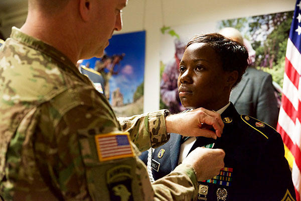 Staff Sgt. Keviann McKelvy, the retention noncommissioned officer assigned to U.S. Army Europe Headquarters and Headquarters Battalion, receives the Army Commendation Medal from Maj. Gen. William K. Gayler. (U.S. Army/Sgt. Daniel Cole)