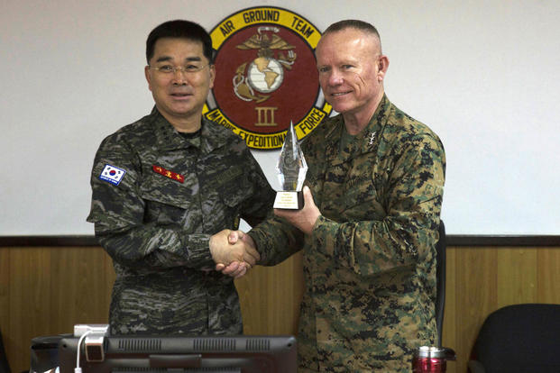 Lt. Gen. Larry Nicholson, the commanding general of III Marine Expeditionary Force, right, presents Lt. Gen. Sang Hoon Lee, commandant of the of the Republic of Korea Marine Corps, left, with a gift Dec. 11, 2015. (Photo: Cpl. Abbey Perria)