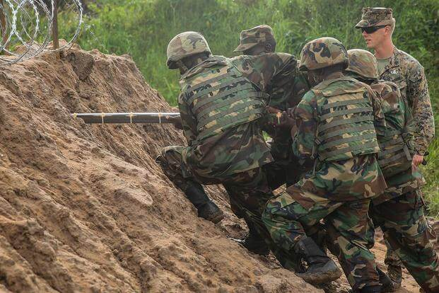 U.S. Marine Sgt. Sam Adkins and Uganda People's Defense Force soldiers emplace explosives through the dirt during a breaching exercise at Camp Singo, Uganda, Dec. 1, 2015. (Photo: Cpl. Olivia McDonald)