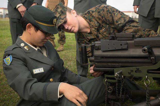 Cpl. Malynn Ochsner shows Japan Ground Self-Defense Force Officer Candidate Ayako Yukawa how to operate a MK19 machine gun, MOD 3 on Camp Kinser, Okinawa, Japan, Jan. 15. (Photo: Cpl. Robert D. Williams Jr.)
