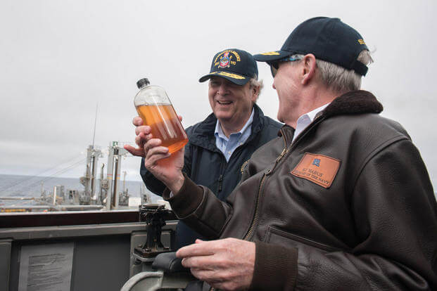 Secretary of the Navy Ray Mabus shows Secretary of Agriculture Tom Vilsack a fuel sample of alternative fuel aboard the guided-missile destroyer USS William P. Lawrence. (Photo: Mass Communication Specialist 2nd Class Armando Gonzales)
