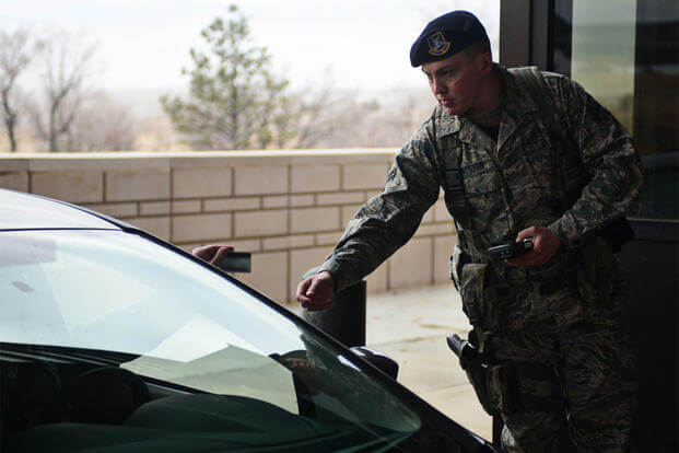 Airman 1st Class Hunter Harveston, 28th Security Forces Squadron response force member, checks an ID card at the Liberty Gate at Ellsworth Air Force Base, S.D., Feb. 12, 2015. (U.S. Air Force photo by Airman 1st Class Zachary Hada/Released)