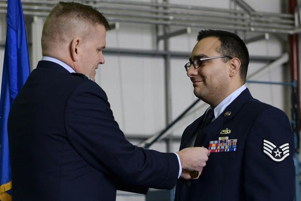 Col. Thomas D. Torkelson, the 100th Air Refueling Wing commander, presents Staff Sgt. Vicente Gomez with the Airman's Medal during a ceremony on Royal Air Force Mildenhall, England. (U.S. Air Force/Senior Airman Victoria H. Taylor)