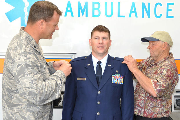 Lt. Col. (Dr.) Joseph Pocreva, left, and Dean Kalinauskas pin new rank on Capt. Zackery Kalinauskas' epaulets during a promotion ceremony outside the Emergency Department. (U.S. Air Force/Steve Pivnick)