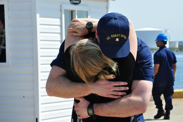 A Coast Guard Cutter Tampa crew member embraces his wife on the pier at Base Portsmouth, Virginia, April 27, 2016. (Photo: Petty Officer 1st Class Melissa Leake)