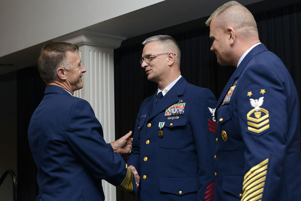 Adm. Paul Zukunft and Coast Guard Reserve Force Master Chief Eric Johnson congratulate PO1 Wilton Terry after presenting him with a Commendation Medal during the 2015 Coast Guard Enlisted Persons of the Year Banquet. (U.S. Coast Guard/CPO Nick Ameen)