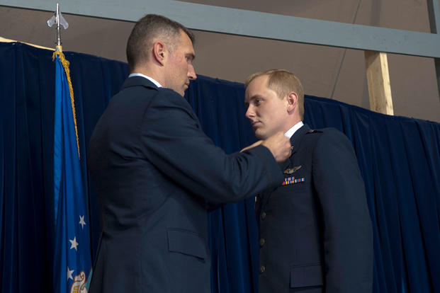 Lt.Col. James Mach pins the rank of captain onto Capt. Norman Popp during a 376th Air Expeditionary Wing promotion and awards ceremony. (U.S. Air Force photo/Staff Sgt. Robert Barnett)