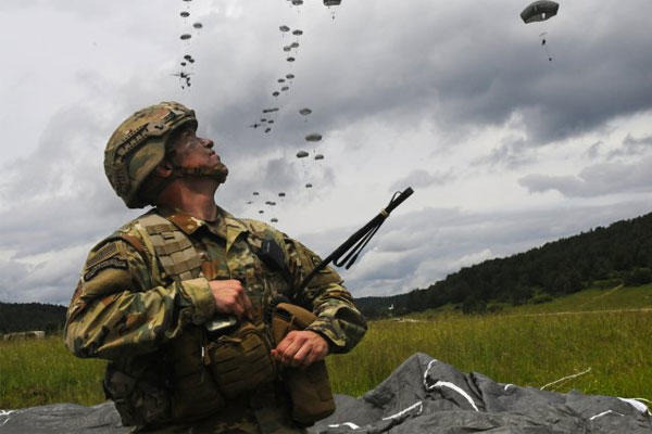 Col. Colin P. Tuley, commander of the 1st Brigade Combat Team, 82nd Airborne Division, recovers his parachute as he watches soldiers descend onto Hohenfels Drop Zone in Germany during Exercise Swift Response, June 15, 2016. (U.S. Army photo/Michael Giles)