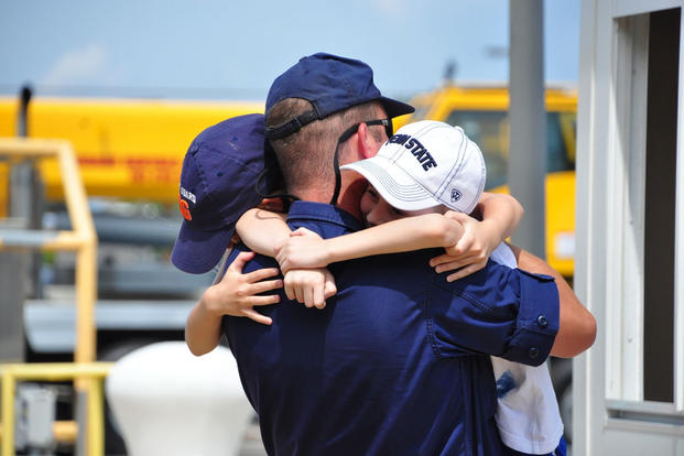 A crewmember from the Coast Guard Cutter Vigorous embraces his children July 11, 2016, in Virginia Beach, Virginia. (Photo: Petty Officer 1st Class Melissa Leake)