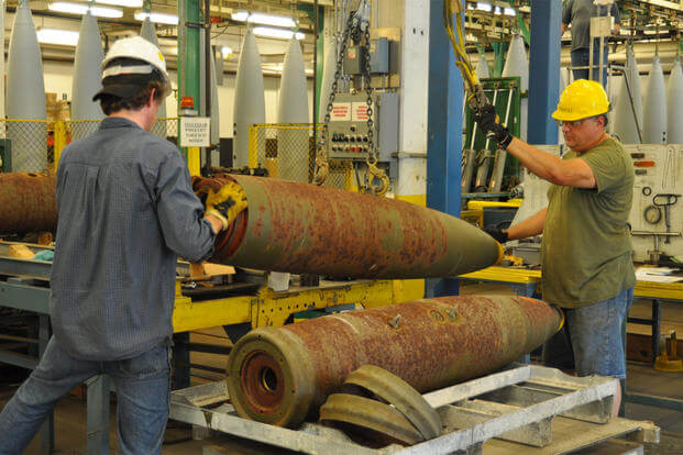 Crane Army Ammunition Activity ordnance professionals prep Mark 80 bombs for renovation before hanging them from the conveyor-type monorail system, July 22, 2015. (U.S. Army photo/Thomas Peske)