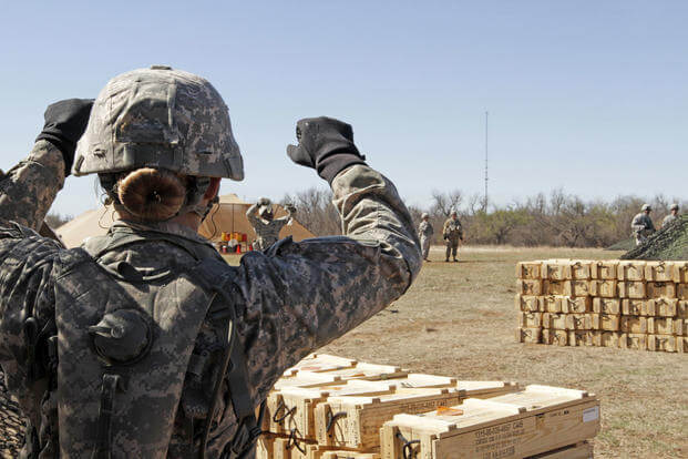 FILE -- A Pfc. gives helpful hints to her teammate holding four excess gunpowder bags that weren't needed for the three-increment charge during live-fire training on the M119A3 howitzer, Fort Sill, March 1, 2016. (U.S. Army photo/Cindy McIntyre)