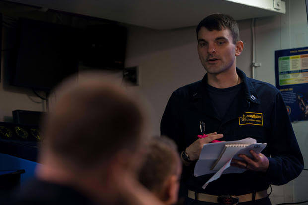 Lt. Damon Goodrich Houska Warfare Tactics Instructor (WTI) of the Naval Surface and Mine Warfighting Development Center (SMWDC) leads a debrief in the ship's classroom of USS Bunker Hill (CG 52), May 3, 2017. (US Navy photo/Ignacio D. Perez)