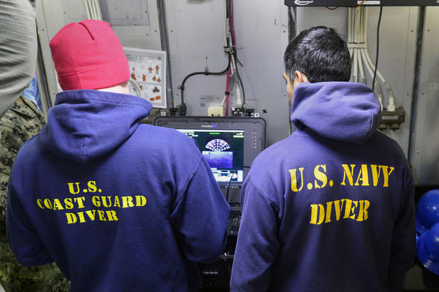 Coast Guard Petty Officer 2nd Class Adam Harris and Navy Petty Officer 2nd Class Matthew Villafuerte, divers deployed on the Coast Guard Cutter Healy, conduct remote operated vehicle, July 24, 2017. (U.S. Coast Guard photo/Meredith Manning)