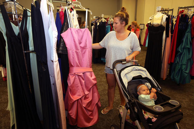 Michelle Walters selects a gown with her baby during Operation Ball Gown at Marine Corps Air Station Cherry Point, N.C., Oct. 2, 2015. (U.S. Marine Corps photo/Lance Cpl. Jason Jimenez)