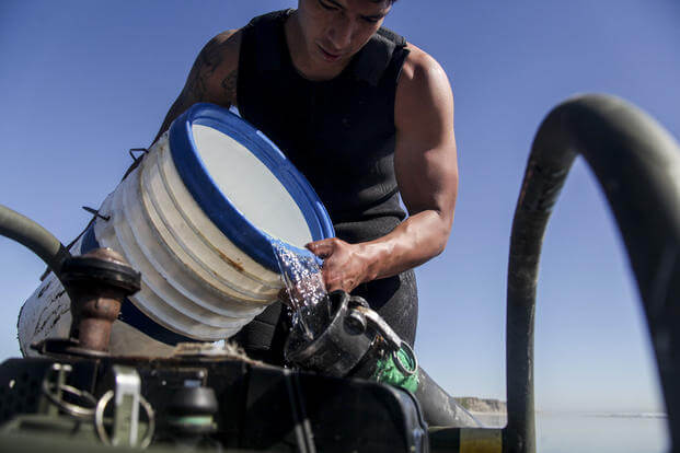 U.S. Marine Lance Cpl. Fransisco pours ocean water into a water purification pipe aboard Camp Pendleton, Calif., March 6, 2015. (U.S. Marine Corps photo/Cpl. Elize McKelvey)