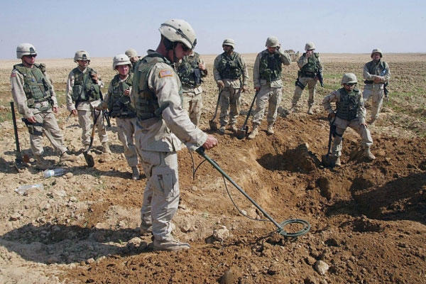 U.S. soldiers watch as a mine sweeper looks for weapons in a hole they dug during a raid on a farm just outside Tikrit, Iraq, on Oct. 9, 2003. (AP)