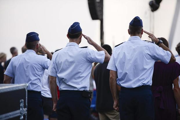 Airmen salute as the colors are presented during a wreath-laying ceremony. (Air Force photo/Tech. Sgt. Joshua L. DeMotts)