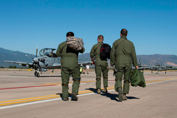 Two pilots from the 81st Fighter Squadron out of Moody Air Force Base, Ga., and an Afghan pilot walk to several A-29B Super Tucanos to prepare for training Sept. 16, 2015, at Peterson Air Force Base, Colo. U.S. Air Force photo/Airman 1st Class Rose Gudex