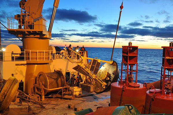 Crew members aboard the Coast Guard Cutter Mackinaw decommission the southern Lake Huron NOAA weather buoy at sunset. (U.S. Coast Guard/PO3 Ryan Alderman)