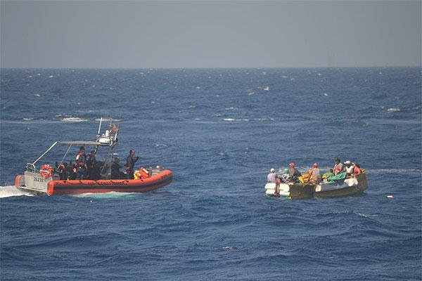 The crew of a Coast Guard cutter approaches a rustic vessel with migrants aboard. U.S. Coast Guard photo.
